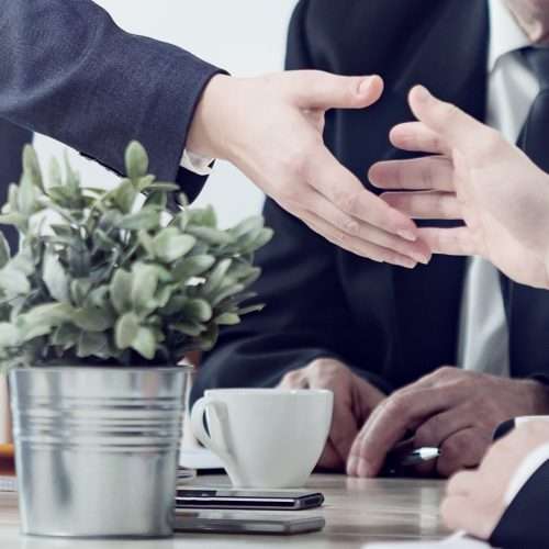 Close-up of businesspeople shaking hands during business meeting